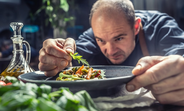A professional chef decorates a meal just before serving it to a customer in a restaurant pub or hotel.