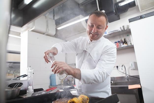 Профессиональный шеф-повар наслаждается работой на своей кухне в ресторане