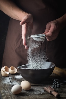 Professional chef hands sifting flour in a bowl for cooking with baking utensils over dark