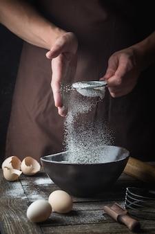 プロのシェフがボウルに小麦粉をふるいにかけ、暗闇で調理器具を使って調理します