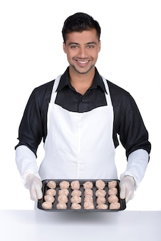 Professional chef is showing food on plate and smiling.