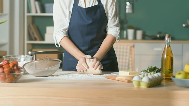 プロのシェフが木製のキッチンテーブルで焼くために生地をこねます。
