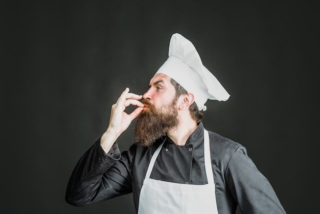 Professional chef man showing sign for delicious male chef in white uniform with perfect sign cook