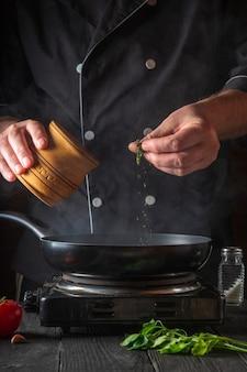 Профессиональный повар наливает специи в кастрюлю
