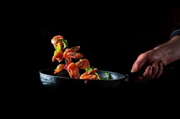 전문 요리사가 허브로 새우를 준비합니다. 어두운 배경에서 해산물, 건강한 채식주의 음식, 음식을 요리하세요. 무료 광고 공간