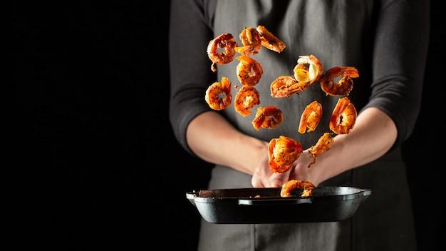 Профессиональный шеф-повар готовит креветки или лангустины