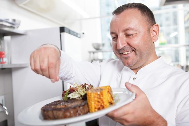 Профессиональный шеф-повар готовит вкусный стейк из говядины с салатом и блюдо из сладкой кукурузы.