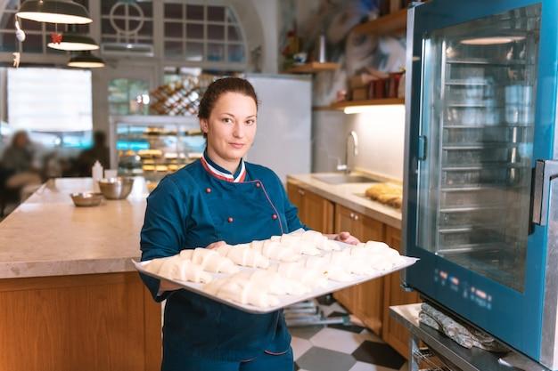 プロのシェフ。オーブンに入れる前にクロワッサンとトレイを保持しているフランスのパン屋のプロのシェフ