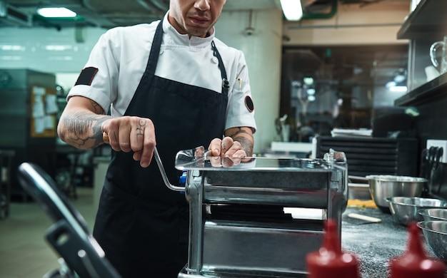 Professional chef rolling a black dough through pasta machine in the restaurant kitchen