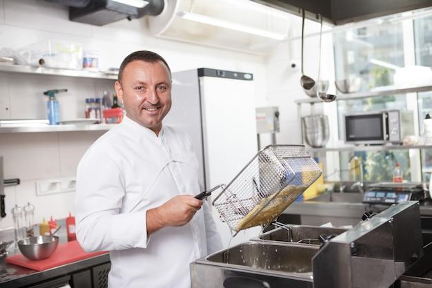 Профессиональный шеф-повар улыбается в камеру, готовит картофель фри на кухне ресторана, копирует пространство