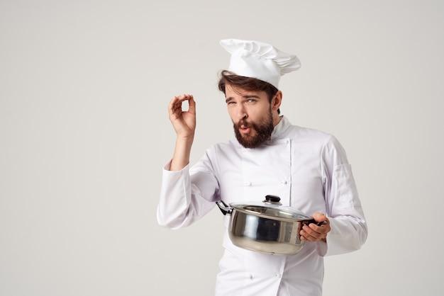 プロのシェフが手に鍋を持って料理を味わうレストランの明るい背景