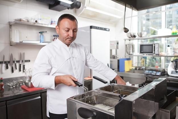 Профессиональный повар, использующий фритюрницу, работает на своей кухне, копирует пространство