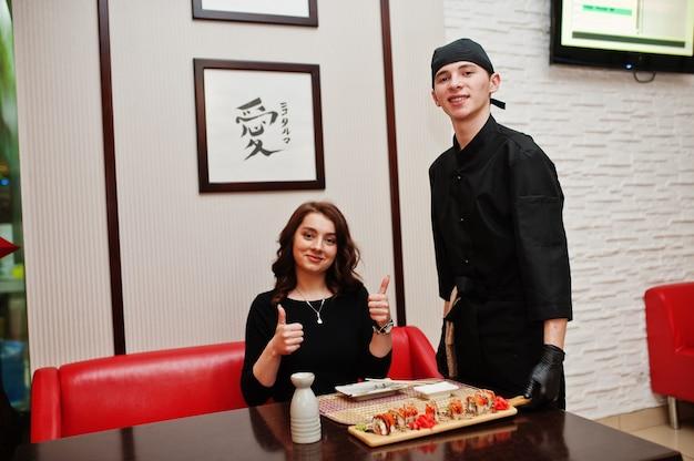 黒のプロのシェフが日本の伝統的な料理のレストランで女性のクライアントに寿司とロールを提供します。