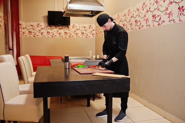 Профессиональный повар в черной одежде готовит суши и роллы на кухне ресторана традиционной японской кухни.
