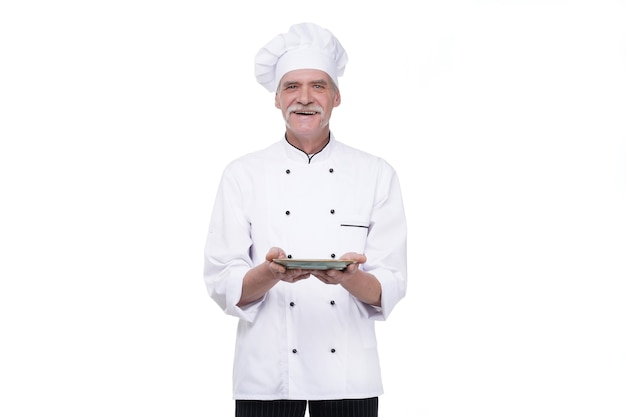 Professional chef in white uniform and hat, holding plate on white wall