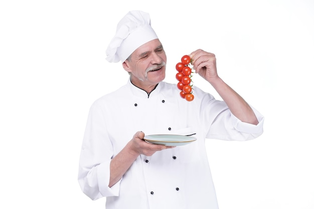 Professional chef in white uniform and hat, holding plate with tomatoes on white wall