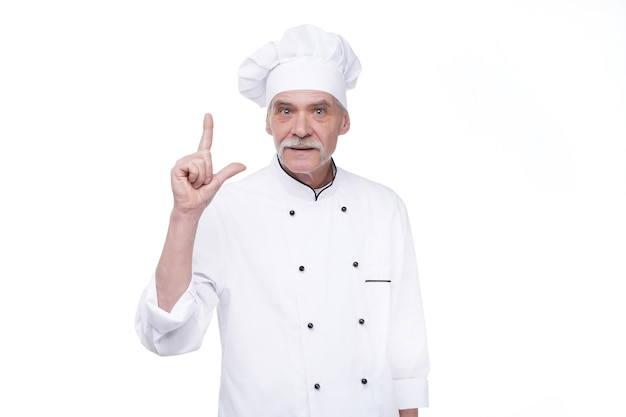 Professional chef in white uniform and hat, on white wall