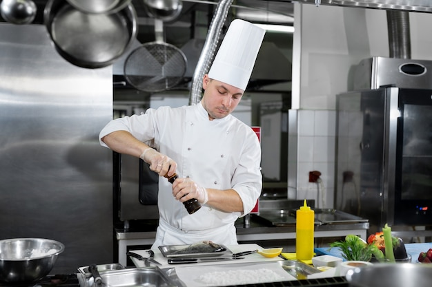 Professional chef in white uniform salts fish