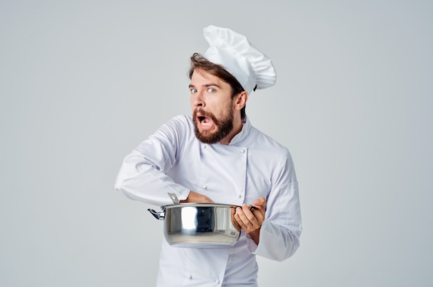 手に鍋を持って料理の仕事をしようとしているプロのシェフ