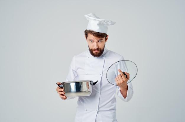 手で鍋料理キッチン明るい背景を持つプロのシェフ