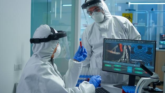 Chimici professionisti in tuta dpi che analizzano lo sviluppo del vaccino puntando sul display del pc in un laboratorio attrezzato