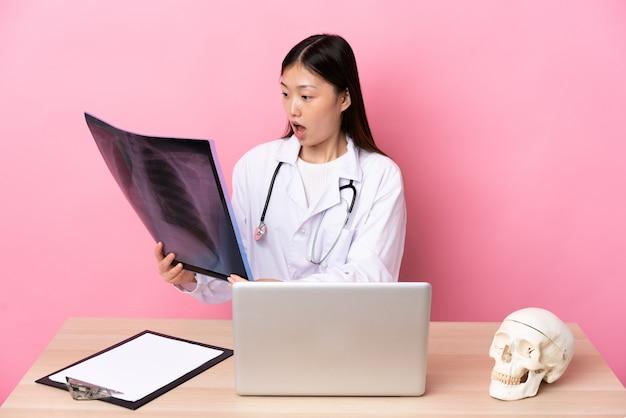 ピンクの背景の上の職場でプロの中国の外傷学者