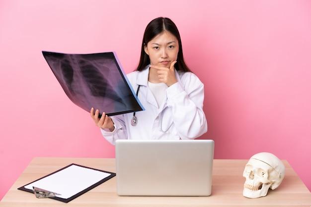 Профессиональный китайский травматолог на рабочем месте, думая идею