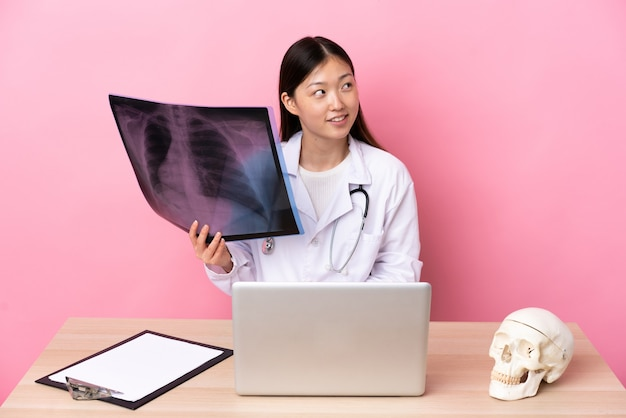 Professional chinese traumatologist in workplace laughing and looking up