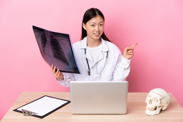 Professional chinese traumatologist in workplace pointing finger to the side