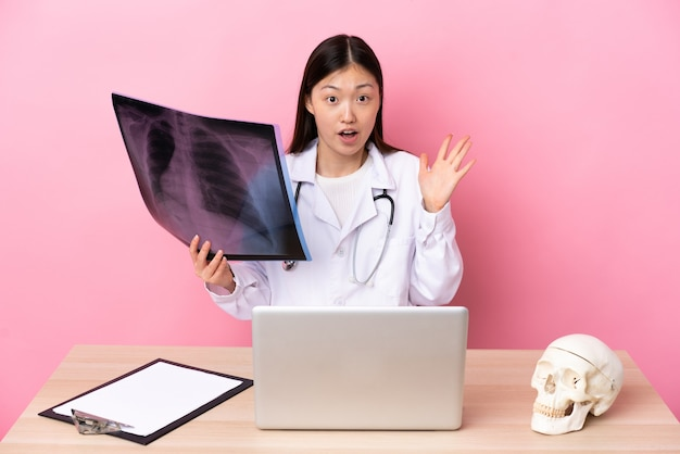 Professional chinese traumatologist in workplace with surprise facial expression