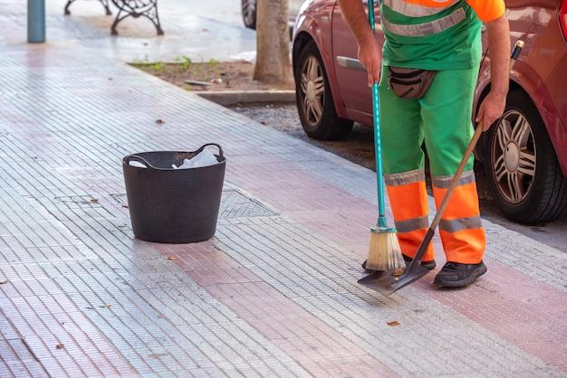 Профессиональный уборщик подметает улицы города с корзиной, чтобы выбрасывать мусор, который он собирает