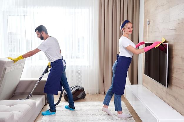 青い制服を着たプロのクリーナーが床を洗い、アパートのリビングルームの家具からほこりを拭き取ります。クリーニングサービスのコンセプト
