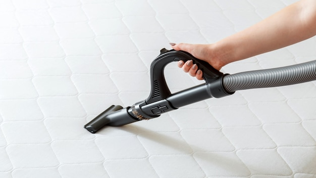 Professional cleaning mattress by vacuum cleaner from dust bacteria dirty. female hand use vacuum cleaner machine for cleaning mattress in apartment. disinfection surfaces. long web banner.