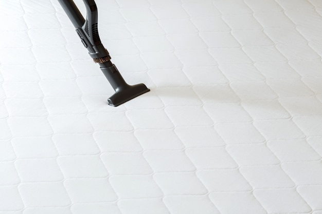 Professional cleaning mattress by vacuum cleaner from dust bacteria dirty. vacuum cleaner machine do disinfection surfaces, cleanliness in hotel apartment. copy space.