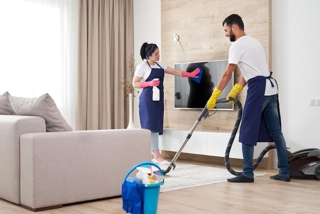 전문 청소 서비스 팀이 현대 아파트의 거실을 청소합니다.