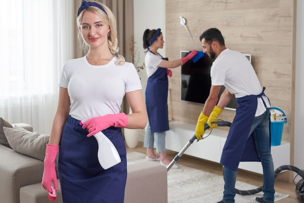 Professional cleaning service team cleans living room in modern apartment