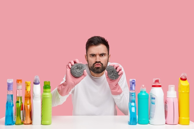 Professional cleaning service. upset bearded man holds two sponges, makes grimace, has sullen expression, wears white clothes