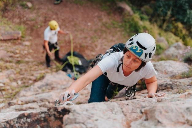 전문 등반가가 안전하게 등반하기 위해 안전에 로프를 걸었습니다.