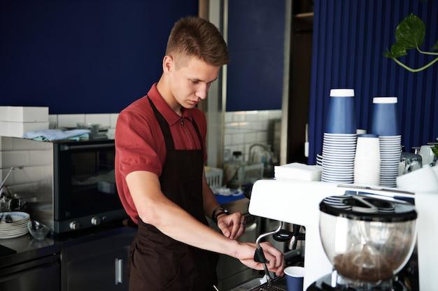 プロのコーヒー醸造。プロのスチームコーヒーマシンでコーヒーを準備する若い訓練を受けたバリスタ。
