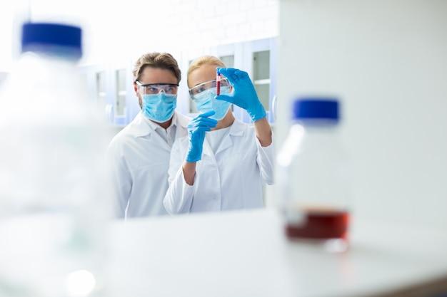 プロフェッショナルなコラボレーション。医療ラボで働いている間、保護具を着用し、血液サンプルを研究している素敵なポジティブな賢い科学者