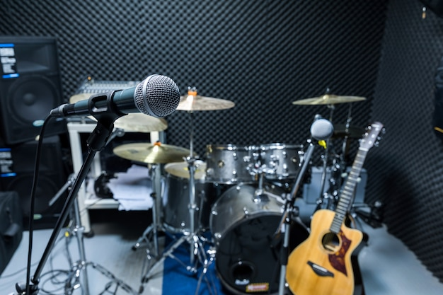 Professional condenser studio microphone, musical concept. recording, selective focus  microphone in radio studio, selective focus microphone and blur musical equipment guitar,