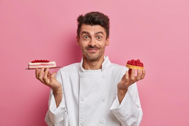 전문 제과점에서 일하고 맛있는 수제 케이크를 들고 레스토랑 주방에서 포즈를 취하고 흰색 유니폼을 입습니다.