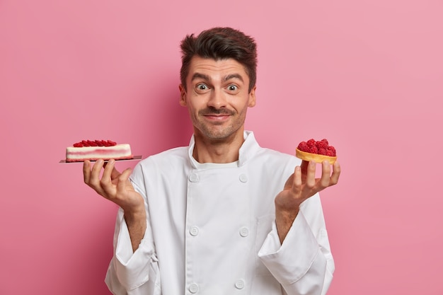 Professional confectioner works in pastry shop, holds yummy handmade cakes, poses in restaurant kitchen, wears white uniform