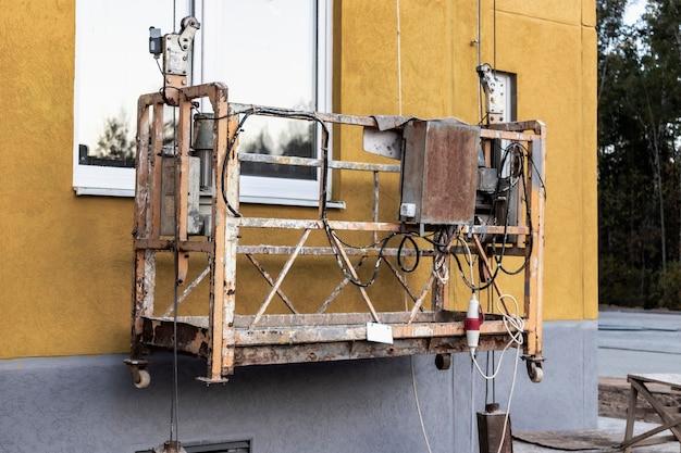 Профессиональная строительная люлька или гондола для строительных работ на высоте многоэтажного дома. промышленное оборудование для работы на высоте.