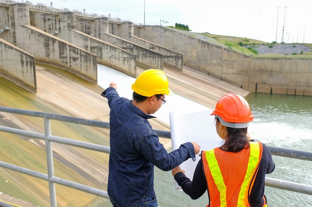 Professional construction woman engineer manager wear safety yellow helmet point building