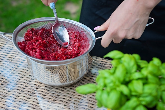 Professional cook hands prepares cranberry berry puree by rubbing berries through a sieve. the process of making marmalade.