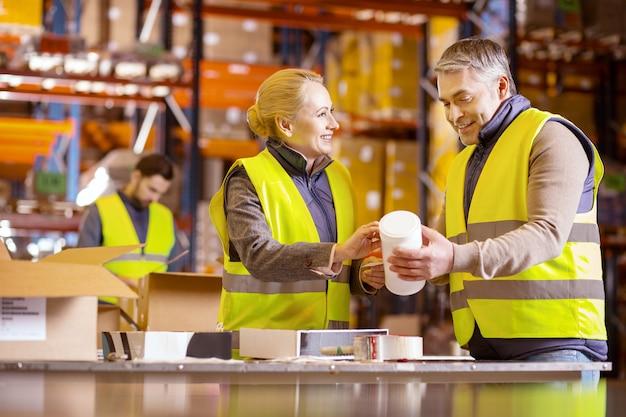 専門家の協力。倉庫で一緒に働いている間、互いに助け合っているポジティブな素敵な人々