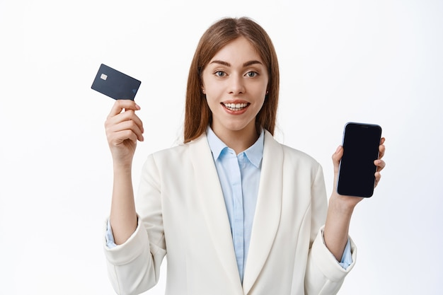 プロの企業の女性、最高経営責任者は白い壁の上にビジネススーツで立って、クレジットカードとスマートフォンの画面を表示します