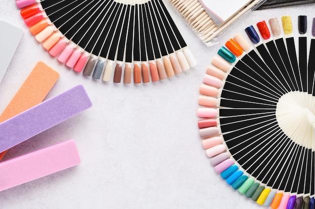 Профессиональные косметические аксессуары для маникюра. палитры образцов искусственных ногтей, пилочки. плоская планировка. скопируйте пространство.