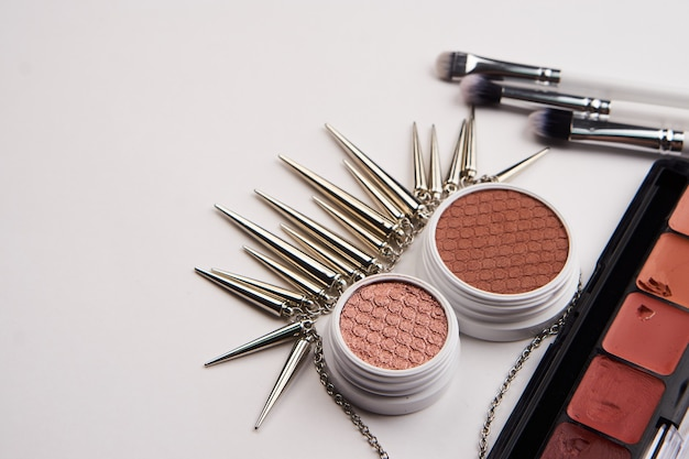 Professional cosmetics and fashionable accessories on a grey table